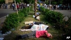 Para pendukung mantan presiden Mohamed Morsi tidur di pinggir jalan dalam protes di luar markas tentara Republican Guard di Nasr City, Kairo (9/7). (AP/Khalil Hamra)