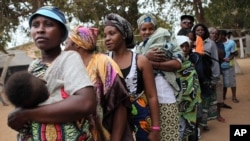 FILE - Angolans queue at a voting station in Kicolo, Luanda, Angola to cast their ballots, Aug. 31, 2012.