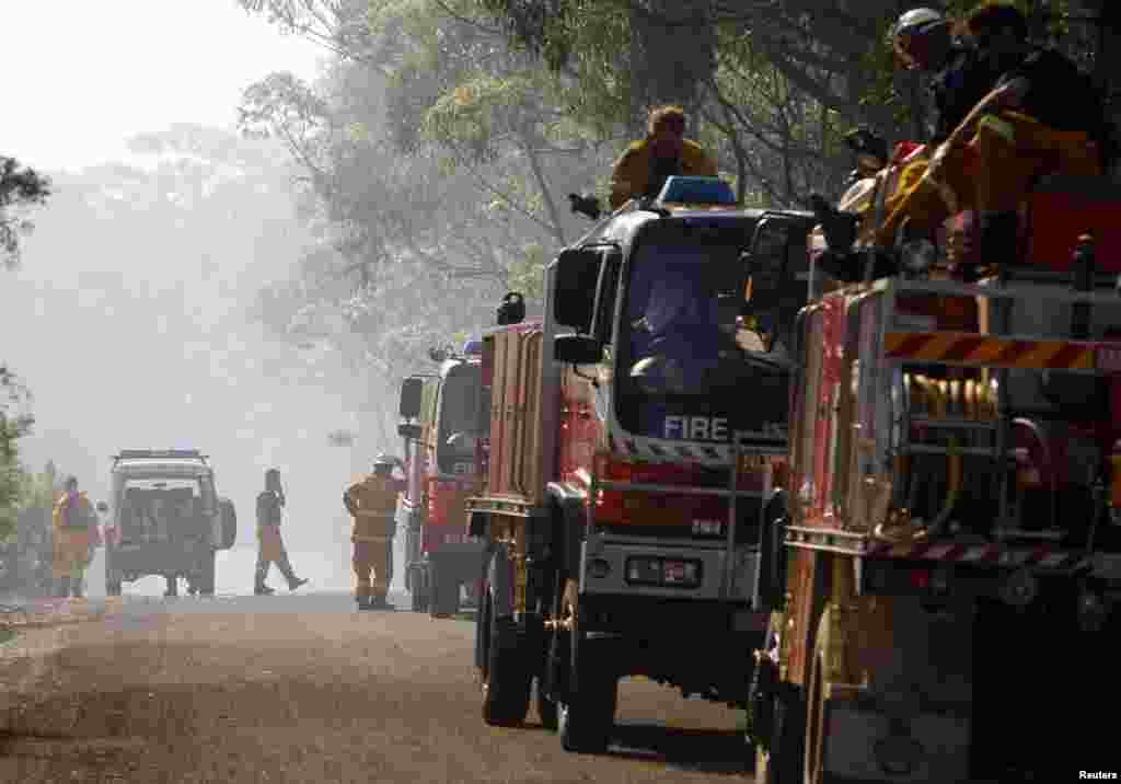 Rural Fire Service frefighters take a break after trying to extinguish a fire approaching homes near the Blue Mountains suburb of Faulconbridge, west of Sydney, Oct. 24, 2013.