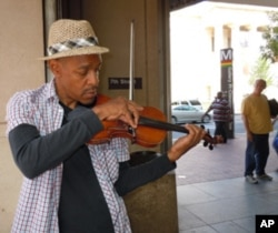 Street musician Raycurt Johnson plays patriotic music near a subway stop in downtown Washington