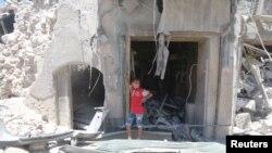 2016年7月11日,叙利亚阿勒颇老城抵抗力量占领区,一个小男孩站在遭到炸弹破坏的地方。