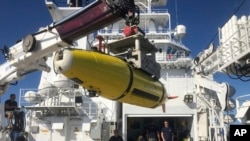 An autonomous underwater vehicle carrying high frequency sonar images of the Japanese aircraft carrier Akagi is loaded onto the research vessel Petrel, Sunday, Oct. 20, 2019, off Midway Atoll in the Northwestern Hawaiian Islands. (AP Photo/Caleb Jones)