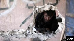 一名叙利亚反政府战斗人员在大马士革郊外乌塔地区的阿滨镇一处地点进行观察。2016年2月26日。