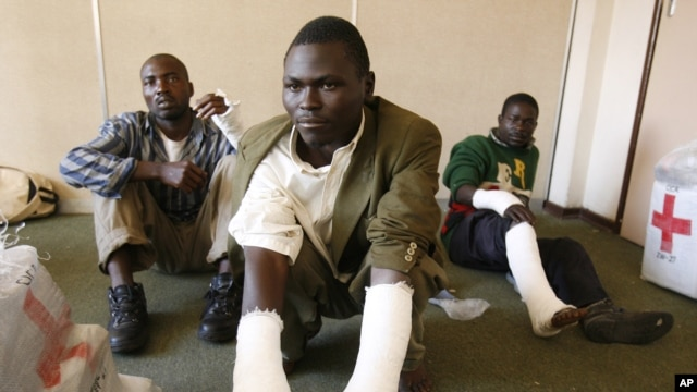 Opposition party Movement for Democratic Change (MDC) supporters from the rural south of the country show their broken limbs from an assault in the capital Harare, May 3, 2008.