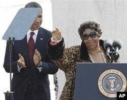 Aretha Franklin acena à multidão sob os aplausos de Obama.