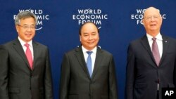 Vietnamese Prime Minister Nguyen Xuan Phuc, center, Chinese Vice Premier Hu Chunhua, left, and Klaus Schwab, executive chair of the World Economic Forum, pose prior to the World Economic Forum on ASEAN Wednesday, Sept. 12, 2018 . (AP Photo/Bullit Marquez, Pool)