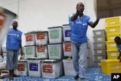Le personnel électoral organise des boîtes de bulletin revenues des bureaux de vote après le dépouillement, à Monrovia (12 octobre 2011)