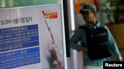A passenger walks past a TV screen broadcasting a news report on North Korea's submarine-launched ballistic missile fired from North Korea's east coast port of Sinpo, at a railway station in Seoul, South Korea, August 24, 2016.