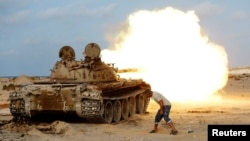 A fighter from Libyan forces allied with the U.N.-backed government fires a shell with a Soviet-made T-55 tank at Islamic State fighters in Sirte, Libya, Aug. 2, 2016.