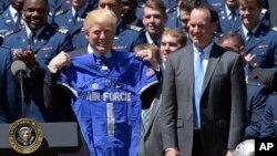 """El presidente Trump muestra una camisa del equipo de fútbol de la Academia de la Fuerza Aérea, que le fue entregada durante la entrega del Trofeo """"Comandante en Jefe""""."""