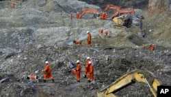 In this photo taken Saturday, Mar. 30, 2013, rescuers search through rocks and debris at a gold mine after a mudslide in Gyama village, in Maizhokunggar County of Lhasa, Tibet.