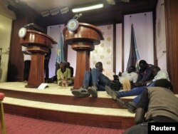FILE - Journalists are seen on the podium following sounds of gunshots before a news conference by South Sudan President Salva Kiir, First Vice President Riek Machar and other government officials inside the Presidential State House in Juba, South Sudan, July 8, 2016.