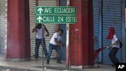 Manifestantes tiran piedras a la policía durante las protestas que derivaron en la derogación de la ley de venta de tierras, anunciada este lunes por el presidente Ricardo Martinelli.
