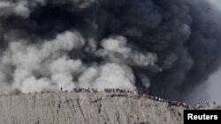 Warga berdiri di pinggir kawah sambil melihat letusan Gunung Bromo, di Probolinggo, 12 Juli 2016.