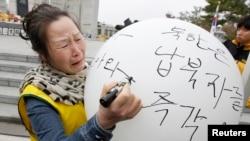 Bà Huh Geum-ja 53 tuổi em của 2 ngư dân Nam Triều Tiên Huh Jung-soo va Huh Yong-ho, mà người ta tin đã bị Bắc Triều Tiên bắt cóc năm 1975, viết những lời nhắn trên chiếc bong bóng trong buổi lễ tưởng niệm các nạn nhân bị miền bắc bắt cóc