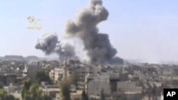 画面显示政府军战机轰炸后,叙利亚东部的代尔祖尔地区升起硝烟