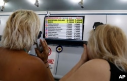 Turkish citizens look at a board showing foreign currency rates inside a currency exchange shop in Ankara, Turkey, Aug. 10, 2018.
