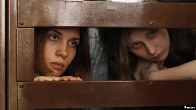 "FILE - Nadezhda Tolokonnikova (L) and Maria Alyokhina, members of female punk band ""Pussy Riot"", look out from the defendent's cell in a courtroom in Moscow, July 30, 2012."