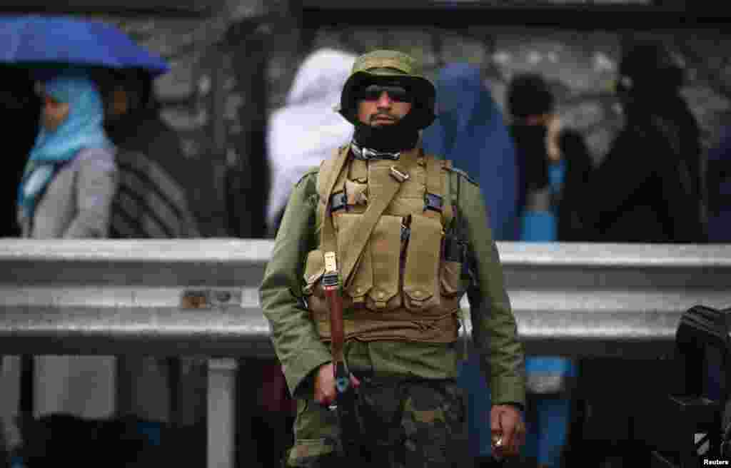 A policeman stands guard outside a polling station in Kabul as Afghans queue to vote outside before it opens.