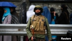A policeman stands guard outside a polling station in Kabul as Afghans wanting to vote queue outside before it opens, April 5, 2014.