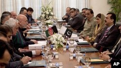Afghan President Hamid Karzai, fourth from left, talks with Pakistan's Prime Minister Yousaf Raza Gilani, right, at the prime minister's house in Islamabad, Pakistan, February 16, 2012.