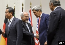 Iranian Foreign Minister Mohammad Javad Zarif (2nd L) shakes hands with U.S. Secretary of State John Kerry next to Chinese Foreign Minister Wang Yi (far L) and French Foreign Minister Laurent Fabius (far R) after a statement on early November 24, 2013 in