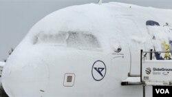 Salju besar menutupi pesawat terbang yang tengah parkir di bandara Schoenefeld di Berlin, Jerman, Senin 20 Desember 2010.