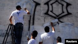 """Miembros de las pandillas borran unos """"grafitis"""" que ellos mismo pintaron como muestra del compromiso en el proceso de paz en El Salvador."""