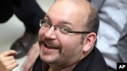 FILE - Jason Rezaian, an Iranian-American correspondent for the Washington Post smiles as he attends a presidential campaign of President Hassan Rouhani in Tehran, Iran.