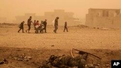 Un groupe de civils passe près du corps d'un militant de l'État islamique en fuite sous des bombardements intensifs de l'EI dans plusieurs zones sous le contrôle de l'armée irakienne, Mossoul, Irak, 2 décembre 2016.