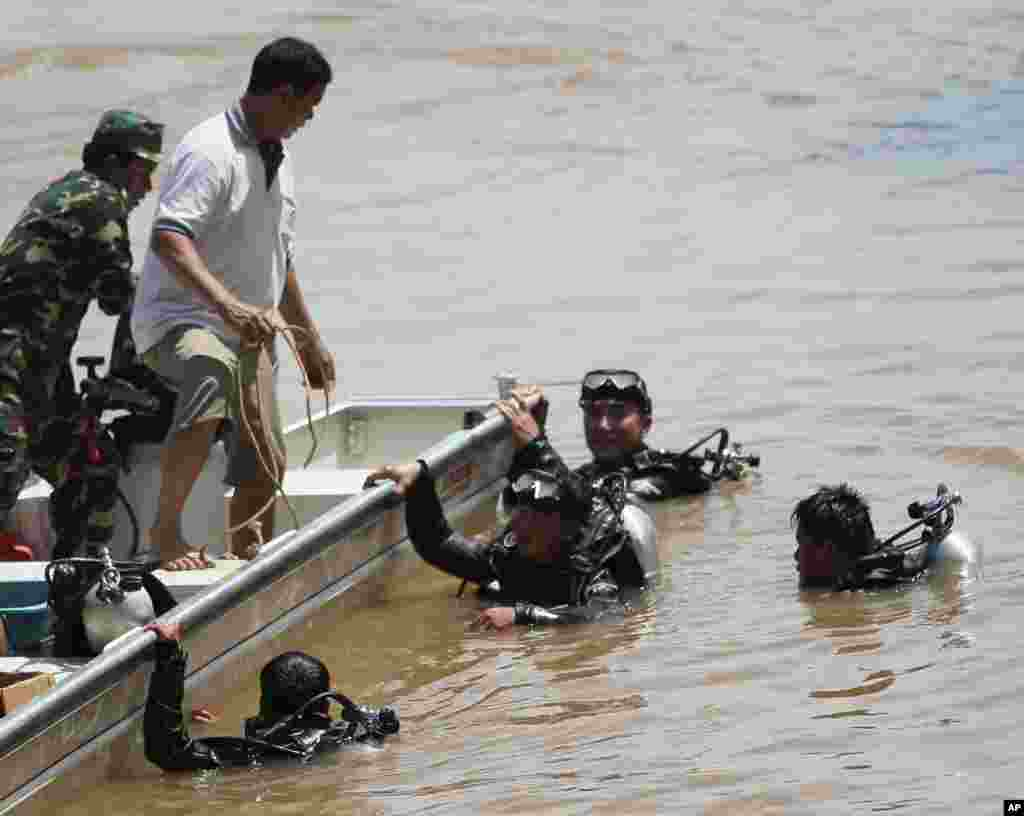 Divers search for bodies of victims of a crashed Lao Airlines plane in the Mekong River in Pakse, Laos, Oct. 17, 2013.