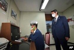 Seorang pejabat pemerintah Korea Selatan melakukan panggilan telepon ke Korea Utara melalui hotline komunikasi khusus saat Menteri Unifikasi Korea Selatan Lee In-young (kanan), mengawasinya saat meninjau kantor tersebut di Panmunjom, Zona Demiliterisasi, Korea Selatan, 16 September 2020.