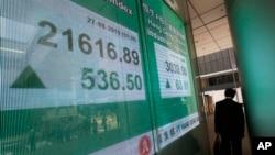 一名男子走过显示香港股市行情的电子屏幕。 (2015年8月27日)
