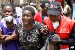 FILE - Red Cross staff console a woman in Nairobi after she viewed the body of a relative killed in al-Shabab's April 2 attack at Garissa University College in northeastern Kenya.