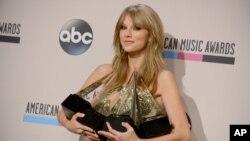 Taylor Swift berpose di belakang panggung dengan empat penghargaan yang diraihnya pada American Music Awards (24/11). (AP/Invision/Jordan Strauss)