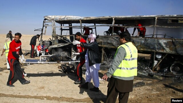 Para petugas mengangkat sisa-sisa jenazah para peziarah Syiah yang terbakar dari dalam bus di Quetta, Pakistan (30/12). Iring-iringan bis para peziarah Syiah ke Iran  menjadi target bom yang diledakkan dari jarak jauh. Dilaporkan 20 orang tewas dan sedikitnya 24 terluka dalam insiden ini.