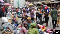 FILE - Pedestrians shop at a busy Balogun Market in Lagos, Nigeria, Sept. 5, 2017. Nigeria announced it will start issuing visas on arrival to all Africans as a way to improve intra-African trade.