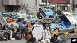 Local residents wait for a ship to travel to a nearby island from the devastated city of Kesennuma, northeastern Japan, just one week after a massive earthquake and resulting tsunami, March 18, 2011
