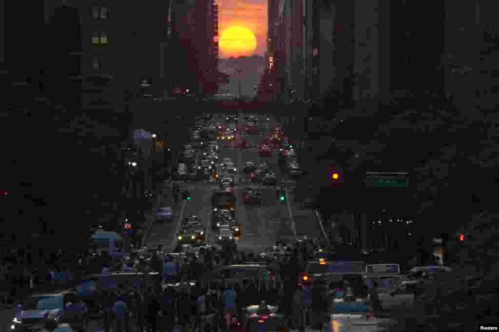 "People take pictures of sunset on 42nd street in New York City, during the biannual occurrence named ""Manhattanhenge"", May 29, 2013. ""Manhattanhenge"", coined by astrophysicist Neil deGrasse Tyson, occurs when the setting sun aligns itself with the east-west grid of streets in Manhattan, allowing the sun to shine down all streets at the same time."