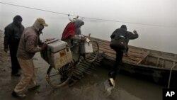 Tim vaksinasi di India mendorong sepeda bermuatan kotak-kotak vaksin ke dalam perahu untuk dibawa ke desa Kosi, 180 km dari Patna. Karena kotak standar styrofoam mudah rusak, WHO memperkirakan, separuh dari jumlah vaksin itu akan rusak dalam perjalanan. Namun, tim mahasiswa dari Universitas Negeri Oklahoma berharap, dengan menggunakan kotak yang bisa dilipat, vaksin yang peka terhadap suhu, akan aman (foto: dok).