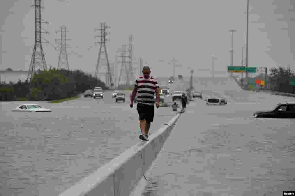 A stranded motorist escapes floodwaters on Interstate 225 after Hurricane Harvey inundated the Texas Gulf coast with rain causing mass flooding, in Houston, Texas.