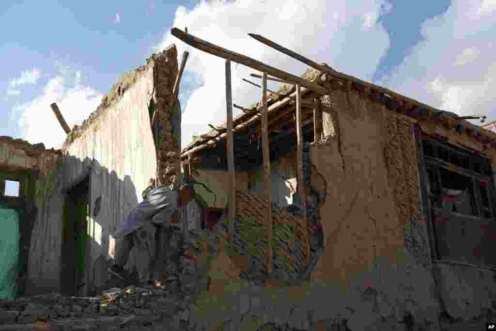 An Afghan boy looks at a damaged house following an earthquake, in Kabul, Oct. 26, 2015.