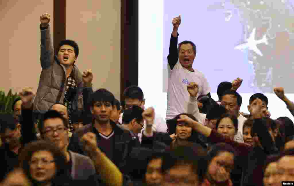 "Family members of passengers onboard flight MH370 raise their fists as they shout ""return our families"" at the Lido Hotel in Beijing, March 22, 2014."
