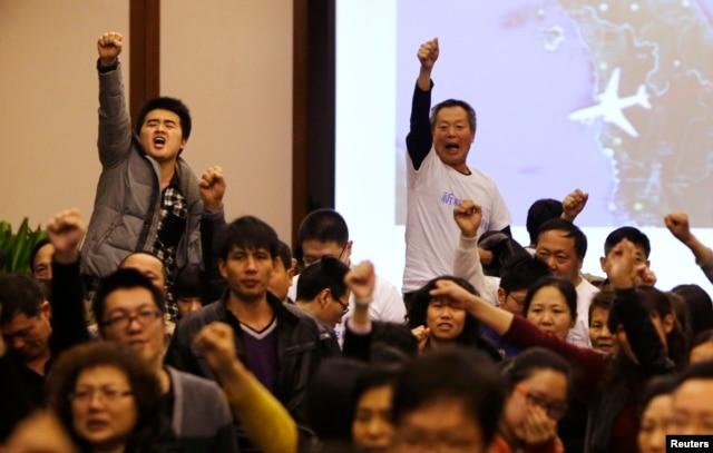 "Family members of passengers onboard Malaysia Airlines Flight MH370 raise their fists as they shout ""return our families"" to protest against the lack of new information after a routine briefing given by Malaysia's government and military representatives at Lido Hotel in Beijing, Mar. 22, 2014."
