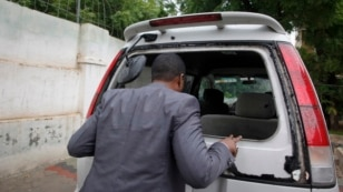 Abdiqadir Dulyar, director for the Somali television station Horn Cable, looks at the smashed window of a car that was carrying journalists working for his station in Mogadishu, May 3, 2016. Unidentified gunmen opened fire on the car last week but no one  was hurt.