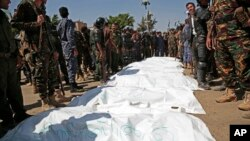 Police stand around bags containing the bodies of nine men, convicted in the killing of a senior Houthi official, after their executions in Sanaa, Yemen, Sept. 18, 2021.