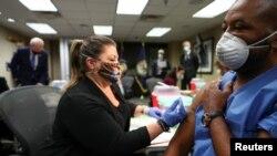 在位於華盛頓市的退伍軍人事務醫療中心,美國總統喬·拜登觀看護士丹尼斯·博希姆為該醫療中心的工作人員、美國陸軍參謀軍士馬文·科尼什接種行新冠疫苗。(2021年3月8日)