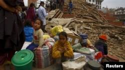 Warga Nepal bersama barang-barang mereka tinggal di luar sebuah kuil yang hancur di lapangan Bashantapur Durbar, Kathmandu, Nepal (25/4).