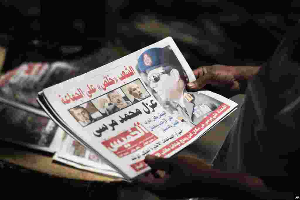 Egyptian man holds a newspaper near Mesaha Square, in Cairo , July 4, 2013. The chief justice of Egypt's Supreme Constitutional Court was sworn in July 4, 2013 as the nation's interim president.