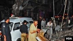 Warga Pakistan berusaha mencari para korban di lokasi serangan bom kembar di kota Peshawar (11/6).